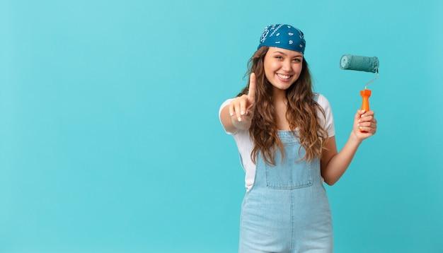 Mulher jovem e bonita sorrindo com orgulho e confiança fazendo o número um e pintando uma parede
