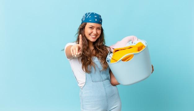 Mulher jovem e bonita sorrindo com orgulho e confiança fazendo o número um e segurando uma cesta de roupas para lavar