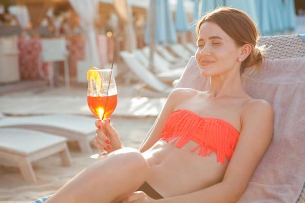 Mulher jovem e bonita sorrindo com os olhos fechados de prazer, descansando na praia. mulher linda tomando um cocktail à beira da piscina no resort de luxo