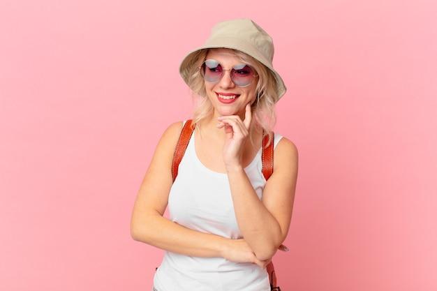 Mulher jovem e bonita sorrindo com uma expressão feliz e confiante com a mão no queixo. conceito de turista de verão