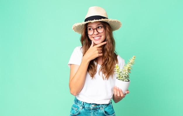 Mulher jovem e bonita sorrindo com uma expressão feliz e confiante, com a mão no queixo e um chapéu de palha segurando um cacto
