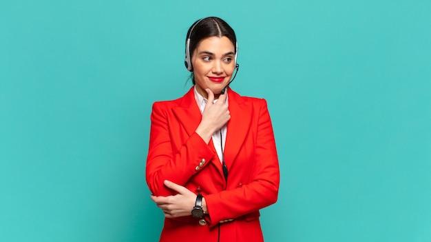 Mulher jovem e bonita sorrindo com uma expressão feliz e confiante com a mão no queixo, pensando e olhando para o lado. conceito de telemarketing