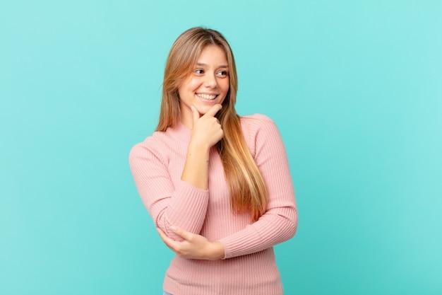 Mulher jovem e bonita sorrindo com uma expressão feliz e confiante com a mão no queixo Foto Premium
