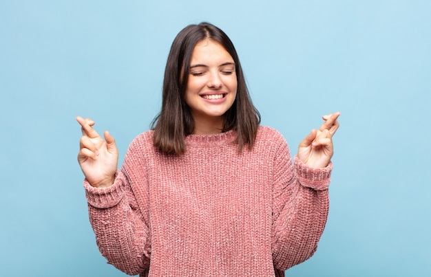 Mulher jovem e bonita sorrindo e cruzando os dedos ansiosamente