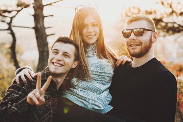 Mulher jovem e bonita sorrindo e olhando em pé entre dois caras bonitos em um dia ensolarado na natureza.