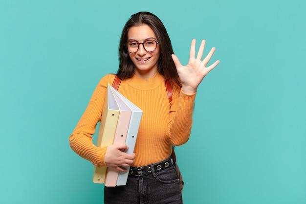 Mulher jovem e bonita sorrindo e parecendo amigável, mostrando o número cinco ou quinto com a mão para a frente, em contagem regressiva. conceito de estudante