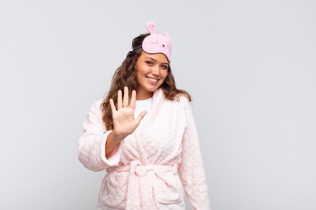 Mulher jovem e bonita sorrindo e parecendo amigável, mostrando o número cinco ou quinto com a mão para a frente, em contagem regressiva de pijama