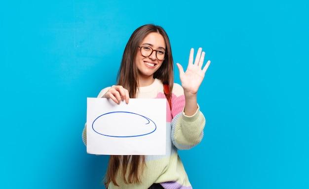 Mulher jovem e bonita sorrindo e parecendo amigável, mostrando o número cinco ou quinto com a mão para a frente, em contagem regressiva