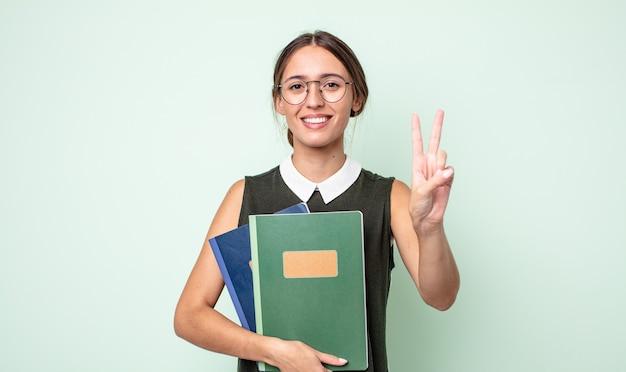 Mulher jovem e bonita sorrindo e parecendo amigável, mostrando o número dois. conceito universitário