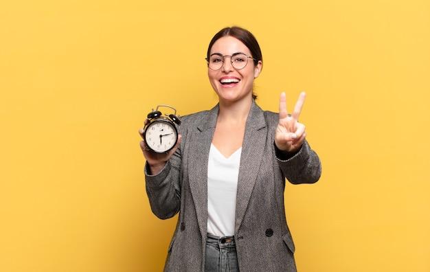 Mulher jovem e bonita sorrindo e parecendo amigável, mostrando o número dois ou o segundo com a mão para a frente, em contagem regressiva
