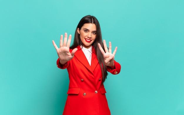 Mulher jovem e bonita sorrindo e parecendo amigável, mostrando o número nove ou nono com a mão para a frente, em contagem regressiva. conceito de negócios