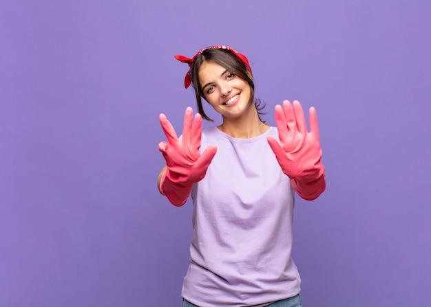 Mulher jovem e bonita sorrindo e parecendo amigável, mostrando o número nove ou nono com a mão para a frente, em contagem regressiva