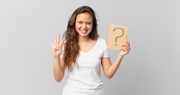 Mulher jovem e bonita sorrindo e parecendo amigável, mostrando o número quatro e segurando um sinal de interrogação