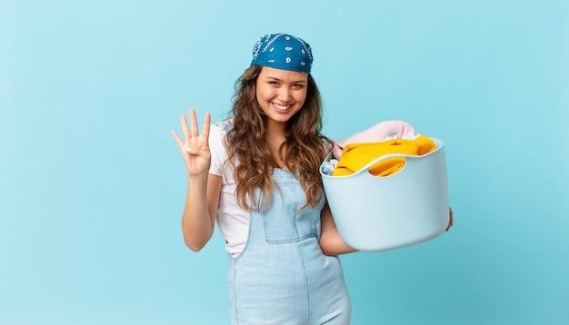 Mulher jovem e bonita sorrindo e parecendo amigável, mostrando o número quatro e segurando uma cesta de roupas para lavar