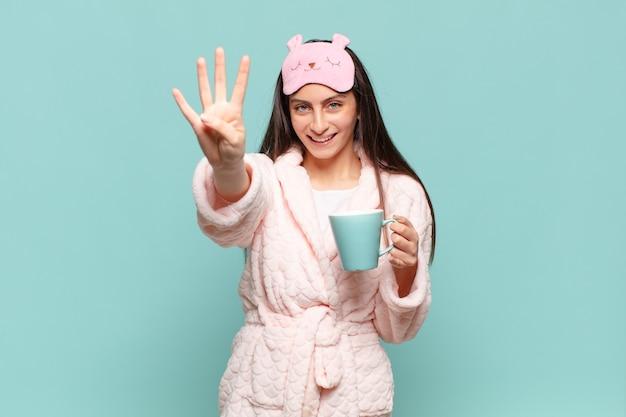 Mulher jovem e bonita sorrindo e parecendo amigável, mostrando o número quatro ou quarto com a mão para a frente, em contagem regressiva. acordar de pijama conceito
