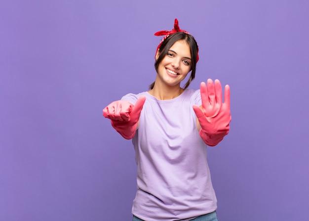 Mulher jovem e bonita sorrindo e parecendo amigável, mostrando o número seis ou sexto com a mão para a frente, em contagem regressiva