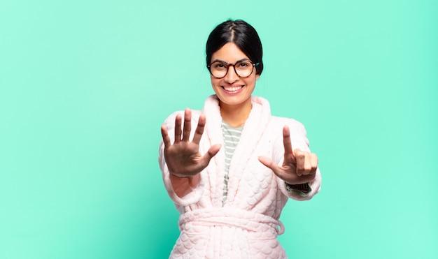 Mulher jovem e bonita sorrindo e parecendo amigável, mostrando o número sete ou sétimo com a mão para a frente, em contagem regressiva. conceito de pijama