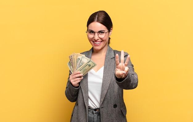 Mulher jovem e bonita sorrindo e parecendo amigável, mostrando o número três ou o terceiro com a mão para a frente, em contagem regressiva