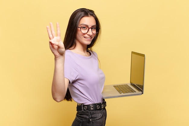 Mulher jovem e bonita sorrindo e parecendo amigável, mostrando o número três ou terceiro com a mão para a frente, em contagem regressiva. conceito de laptop