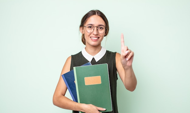 Mulher jovem e bonita sorrindo e parecendo amigável, mostrando o número um. conceito universitário