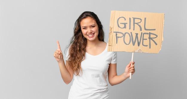 Mulher jovem e bonita sorrindo e parecendo amigável, mostrando o número um e segurando uma bandeira do poder feminino