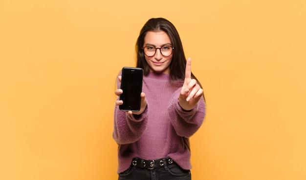Mulher jovem e bonita sorrindo e parecendo amigável, mostrando o número um ou primeiro com a mão para a frente, em contagem regressiva. conceito de tela do telefone