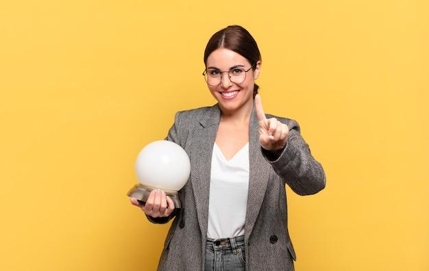 Mulher jovem e bonita sorrindo e parecendo amigável, mostrando o número um ou primeiro com a mão para a frente, em contagem regressiva