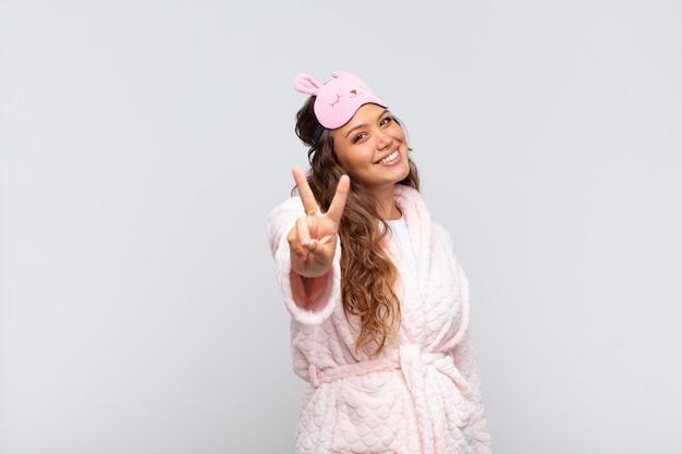 Mulher jovem e bonita sorrindo e parecendo feliz, despreocupada e positiva, gesticulando vitória ou paz com uma mão de pijama