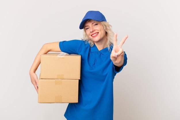 Mulher jovem e bonita sorrindo e parecendo feliz, gesticulando vitória ou paz. conceito de entrega de pacote
