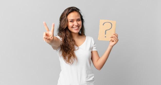 Mulher jovem e bonita sorrindo e parecendo feliz, gesticulando vitória ou paz e segurando um sinal de interrogação