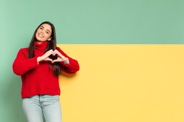 Mulher jovem e bonita sorrindo e se sentindo feliz, fofa, romântica e apaixonada, fazendo formato de coração com as duas mãos. copie o espaço para colocar o seu conceito