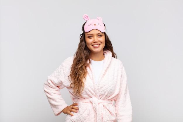 Mulher jovem e bonita sorrindo feliz com a mão no quadril e com uma atitude confiante, positiva, orgulhosa e amigável de pijama
