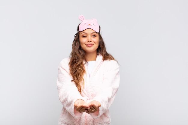Mulher jovem e bonita sorrindo feliz com um olhar amigável, confiante e positivo, oferecendo e mostrando um objeto ou conceito de pijama