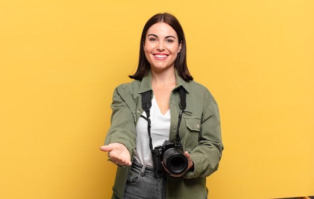 Mulher jovem e bonita sorrindo feliz com um olhar amigável, confiante e positivo, oferecendo e mostrando um objeto ou conceito