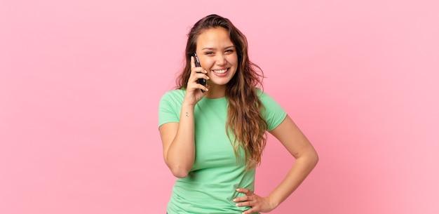Mulher jovem e bonita sorrindo feliz com uma mão no quadril, confiante e segurando um telefone inteligente