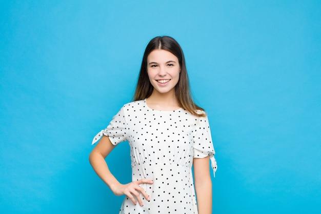 Mulher jovem e bonita sorrindo feliz com uma mão no quadril e uma atitude confiante, positiva, orgulhosa e amigável contra a parede azul