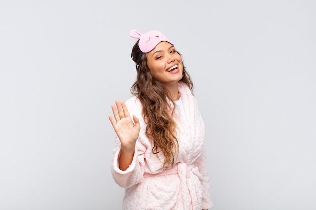 Mulher jovem e bonita sorrindo feliz e alegre, acenando com a mão, dando as boas-vindas e cumprimentando você ou dizendo adeus de pijama