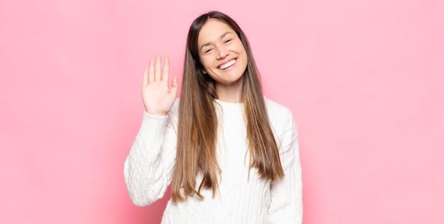 Mulher jovem e bonita sorrindo feliz e alegre, acenando com a mão, dando as boas-vindas e cumprimentando você ou dizendo adeus