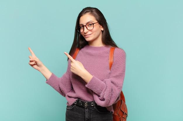 Mulher jovem e bonita sorrindo feliz e apontando para o lado e para cima com as duas mãos mostrando o objeto no espaço da cópia