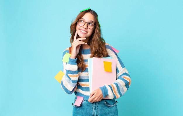 Mulher jovem e bonita sorrindo feliz e sonhando acordada ou duvidando com uma bolsa e segurando livros