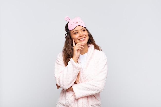 Mulher jovem e bonita sorrindo feliz e sonhando acordada ou duvidando, olhando para o lado de pijama