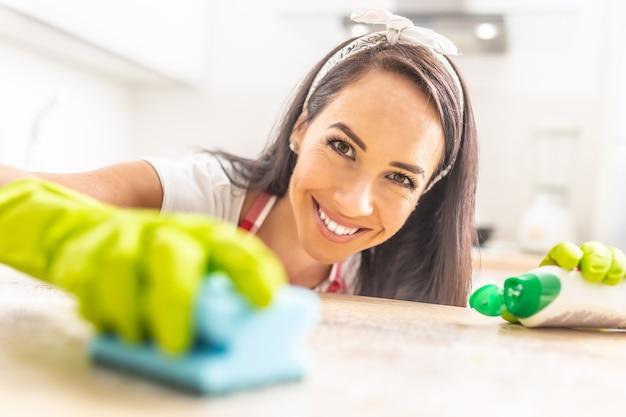 Mulher jovem e bonita sorrindo para a câmera enquanto limpa a superfície de uma mesa com uma esponja em suas luvas de borracha.