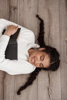 Mulher jovem e bonita sorrindo, segurando o livro, deitado no chão de madeira