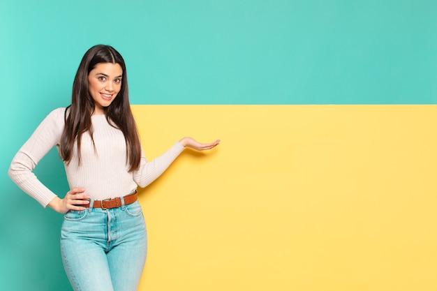Mulher jovem e bonita sorrindo, sentindo-se confiante, bem-sucedida e feliz, mostrando o conceito ou ideia no espaço da cópia ao lado. copie o espaço para colocar o seu conceito