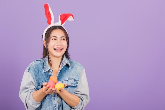Mulher jovem e bonita sorrindo usando orelhas de coelho e jeans segurando um presente de ovos de páscoa coloridos nas mãos