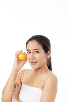 Mulher jovem e bonita spa com laranja na mão, isolada no fundo branco