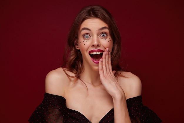 Mulher jovem e bonita surpresa com cabelo castanho ondulado olhando para a câmera com os olhos arregalados e a boca aberta, mantendo a palma da mão perto do rosto, vestida com uma blusa preta elegante com pontos vermelhos sobre fundo clarete