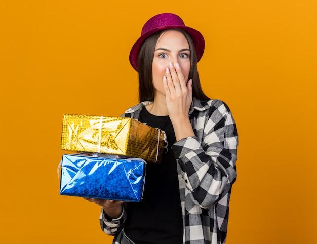 Mulher jovem e bonita surpresa com chapéu de festa segurando caixas de presente, boca coberta com a mão isolada na parede laranja