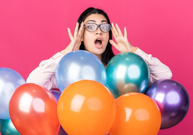 Mulher jovem e bonita surpresa com óculos em pé atrás de balões isolados na parede rosa