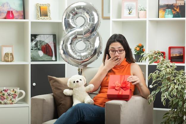 Mulher jovem e bonita surpresa de óculos colocando a mão na boca e olhando para a caixa de presente sentada na poltrona na sala de estar em março, dia internacional da mulher